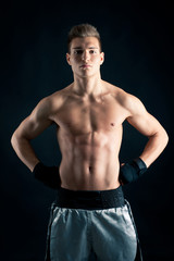 Sportsman boxer intense portrait against black background.