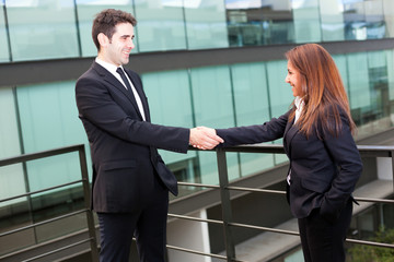 Businesspeople shaking hands at modern office