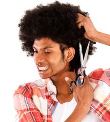 Black man cutting his afro