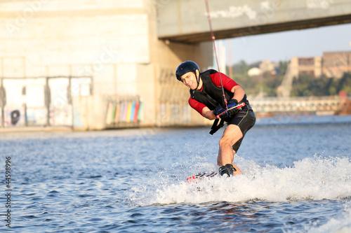 Fotobehang Water Motorsp. Wakeboarder surfing across a river