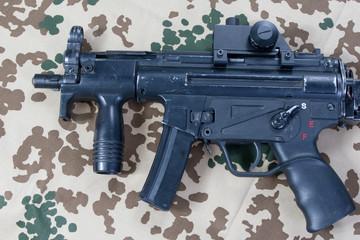 modern submachine gun MP5 on desert camouflaged background