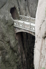 Mountain stone bridge above rocky precipice, China
