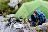 Outdoors man cooking beside his camping tent