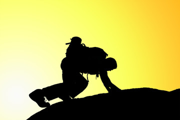Silhouette of climbing young adult at the top of summit