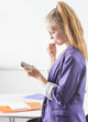 Young adult female holding cellphone in office