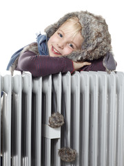 Cute girl with pelt cap leans over a radiator to keep warm