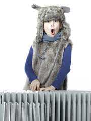 Cute girl with pelt cap leaning over a radiator and shouting