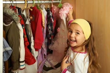 Kind bei ihrem Kleiderschrank