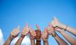Viele Hände zeigen Daumen hoch vor blauem Himmel