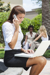 Young Woman On Cell Phone Using Laptop Computer