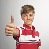 Happy casual young man showing thumb up and smiling