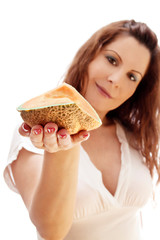 cute woman is offering a slice of cantaloupe