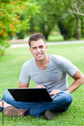 Young student sitting on the grass