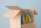 Multicolored clothes in a wardrobe box for easy moving poster