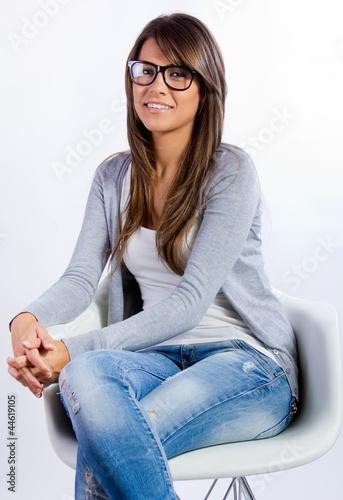 Mujer joven morena con gafas sentada en una silla