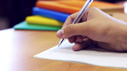 Human hand writing task on the copybook with books behind