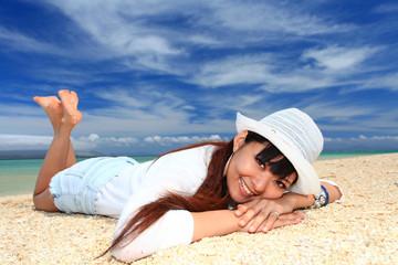 砂浜に寝転がる笑顔の女性