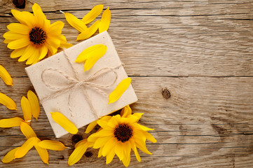 Ornamental sunflowers and gift box on wooden background