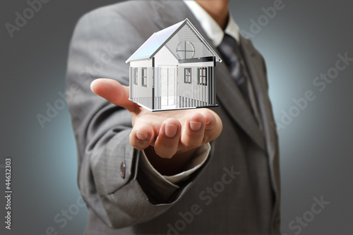 Business man present  diamond house model