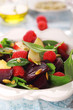 Fresh vegetarian salad with beets, apples and raspberries.