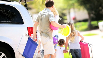 Young Family Packing Car for Trip to Beach