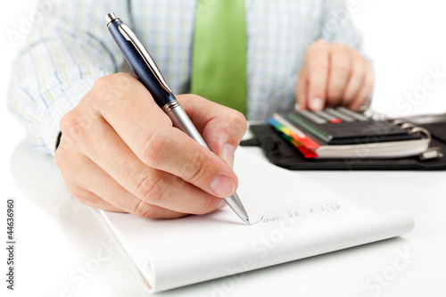 Businessman counting on calculator.