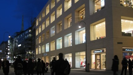 Tourists go on Kartner Strasse near shop