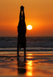female gymnast doing a handstand in sunset