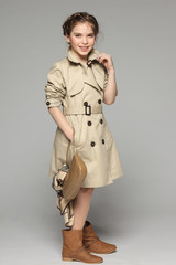 Lovely girl wearing beige trench coat holding handbag