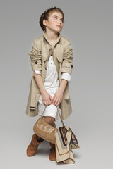 Lovely girl wearing beige trench coat looking to side