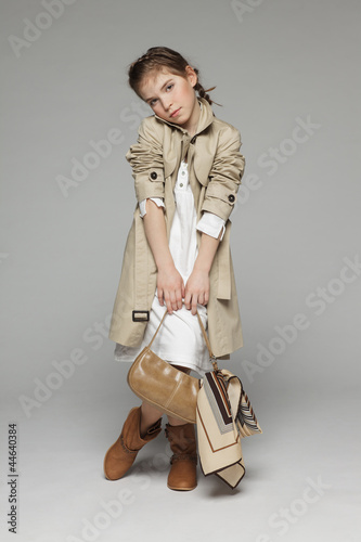 Little girl wearing trench coat holding handbag