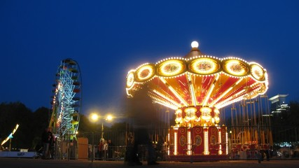 People ride on shone chairoplane in night