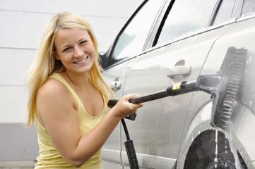 Junge Frau bei Wagenwäsche