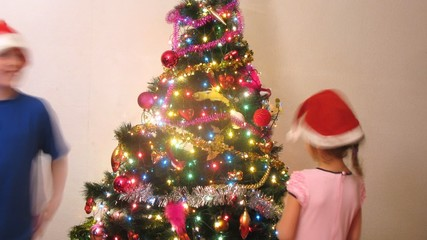Girl and boy decorate New Year tree in hats of Santa Claus