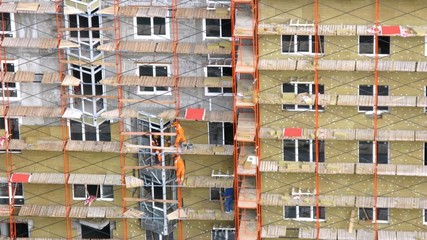 Workers mount scaffold at height on wall of house