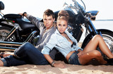 Extreme couple sitting by motorcycle. Adventure and travel