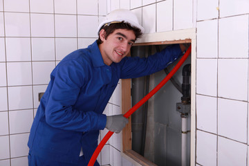 Electrician feeding red pipe behind a tiled wall