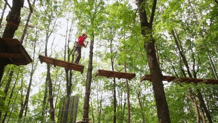 girl goes on boards suspended in wood, strong keeping for ropes
