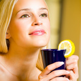 Cheerful blond woman with cup of tea, indoor