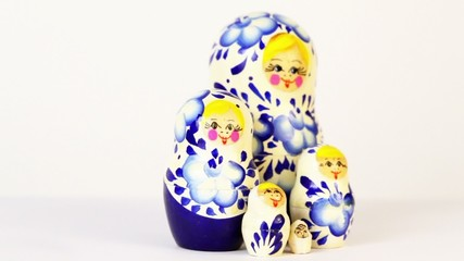 Four russian nesting dolls stand grouped and spin