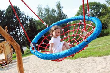 Mädchen sitzt in einer Nestschaukel auf einem Spielplatz