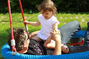Vater spielt mit seiner Tochter auf einem Spielplatz