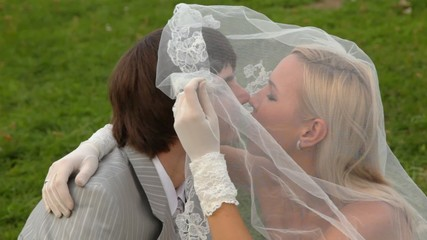 Newly-married couple sits and kisses under veil of bride