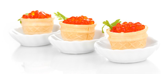 Red caviar in tartlets on little white saucers isolated on