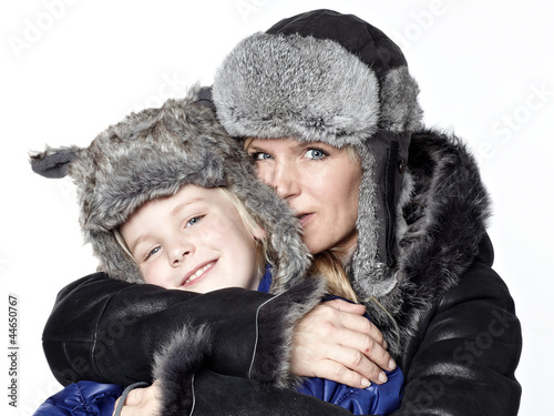 Mother and daughter in warm winter coats huggle together