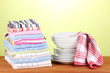 kitchen towels with dishes on green background close-up
