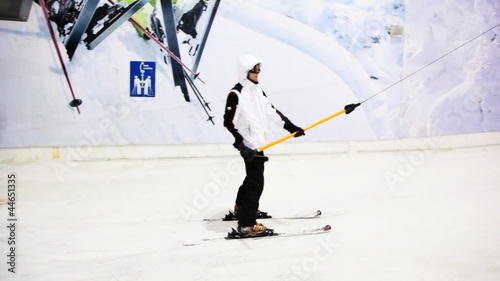skier sportsman sitting on handle goes up hill