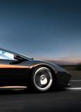 Schwarzer italienischer Sportwagen fährt schnell auf einer Straße