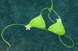 Green bikini floating with pulmeria flowers