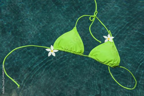 Green bikini floating with pulmeria flowers